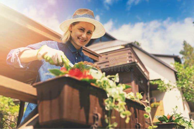 Glimlachende vrouw die bloemen in dozen op terrastraliewerk planten royalty-vrije stock foto's