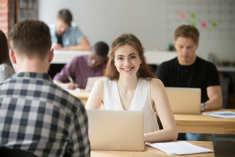 Glimlachende vrouw die camerazitting bekijken bij bureau in mede-werkt stock afbeelding