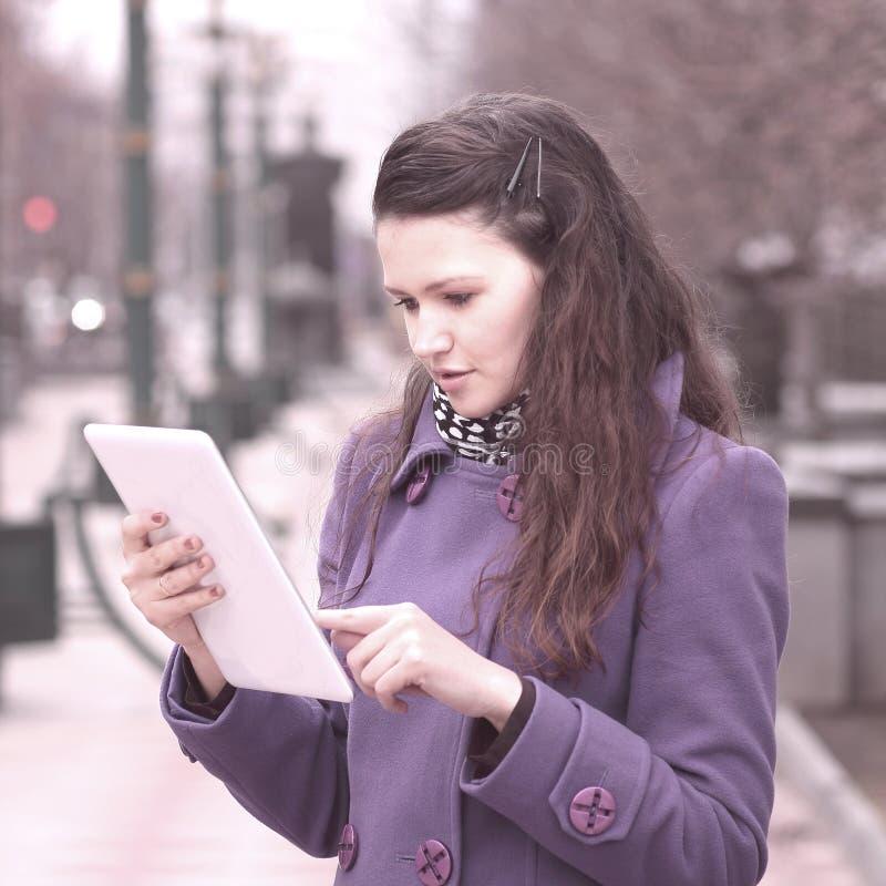 Glimlachende vrouw die digitale tablet gebruiken die zich op stadsstraat bevinden royalty-vrije stock afbeeldingen