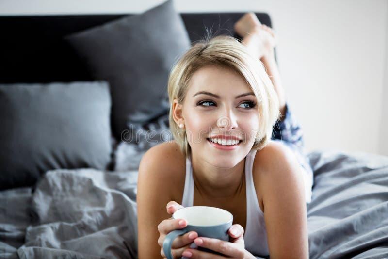 Glimlachende vrouw die een koffie drinken die in bed liggen stock foto