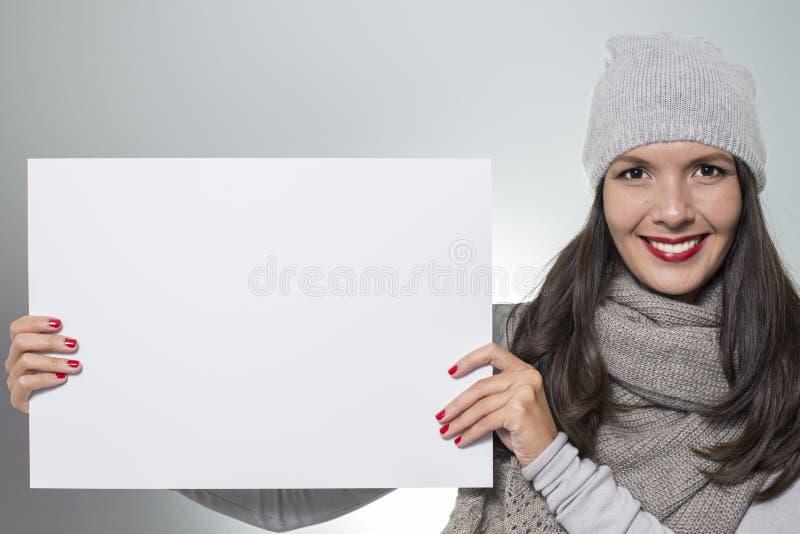 Glimlachende vrouw die een leeg teken houden stock foto