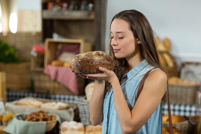 Glimlachende vrouw die een rond brood van brood ruiken bij teller royalty-vrije stock foto