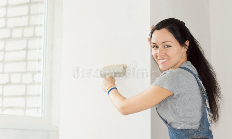 Glimlachende vrouw die een sectie van muur schilderen royalty-vrije stock foto