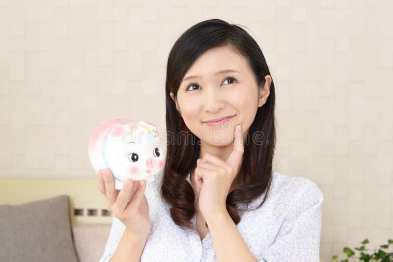 Glimlachende vrouw die een spaarvarken houden stock fotografie