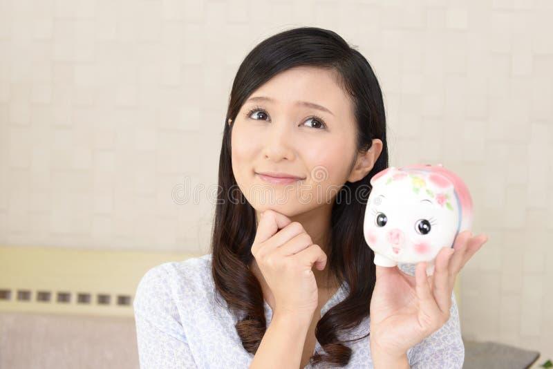 Glimlachende vrouw die een spaarvarken houden royalty-vrije stock afbeeldingen