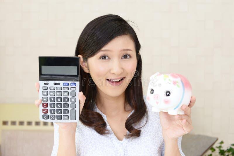 Glimlachende vrouw die een spaarvarken houden stock afbeeldingen