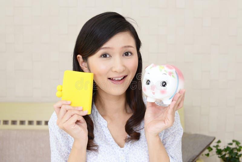 Glimlachende vrouw die een spaarvarken houden royalty-vrije stock foto