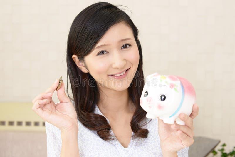 Glimlachende vrouw die een spaarvarken houden royalty-vrije stock fotografie