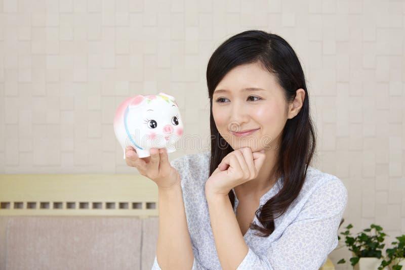 Glimlachende vrouw die een spaarvarken houden stock afbeelding