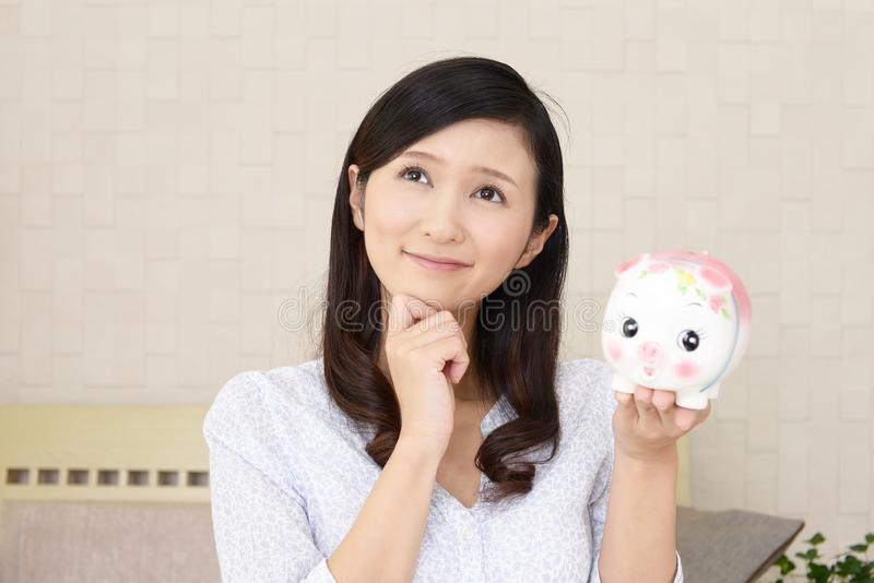 Glimlachende vrouw die een spaarvarken houden stock foto's