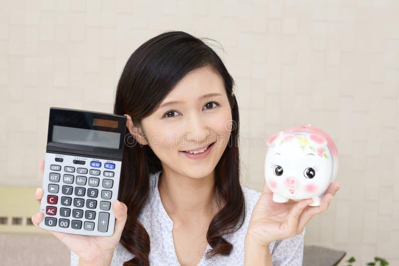 Glimlachende vrouw die een spaarvarken houden royalty-vrije stock afbeelding