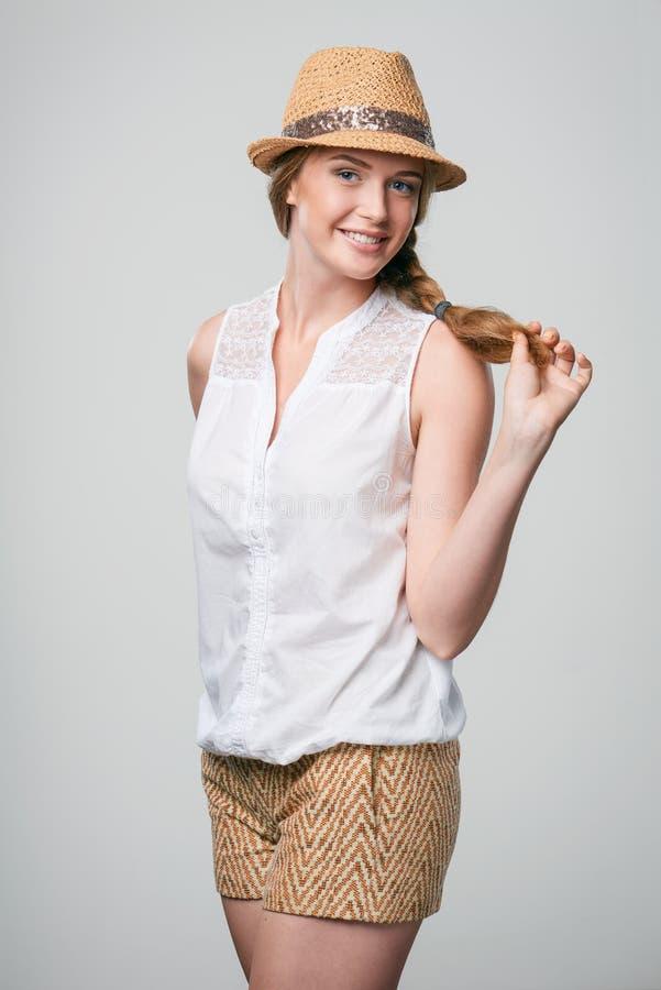 Glimlachende vrouw die fedorahoed dragen van het de zomerstro royalty-vrije stock fotografie