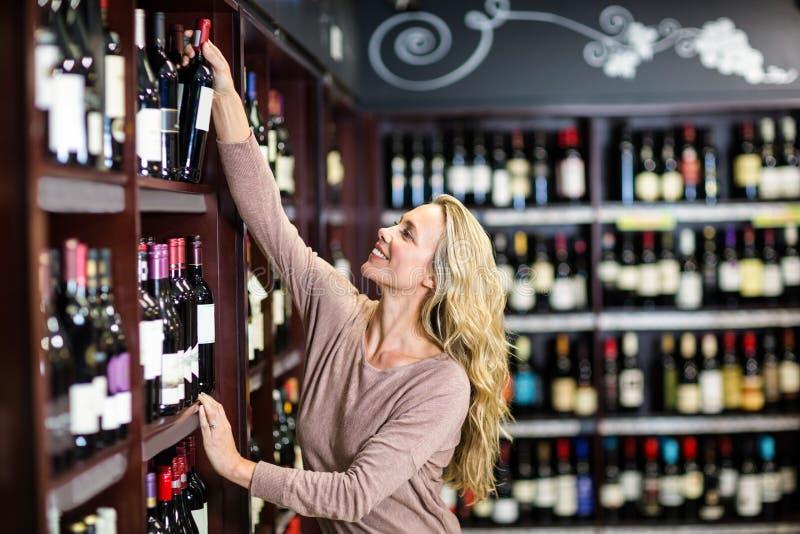Glimlachende vrouw die fles wijn uitkiezen stock foto's