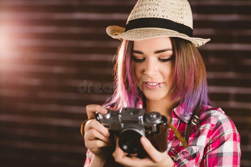 Glimlachende vrouw die foto's van uitstekende camera controleren stock foto's