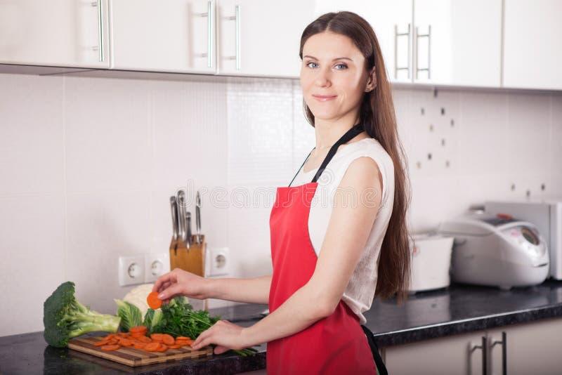 Glimlachende vrouw die gezond voedsel in keuken maken royalty-vrije stock foto's