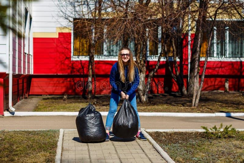 Glimlachende vrouw die grote plastic zakken met huisvuil houden stock foto