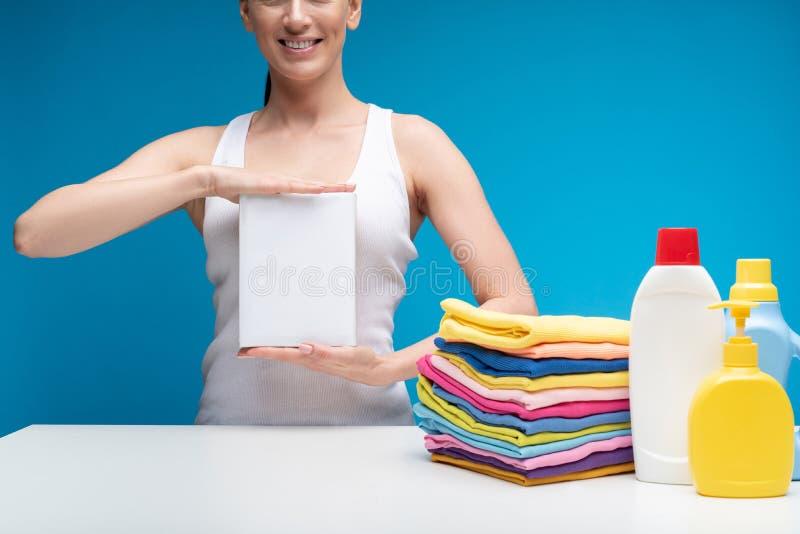 Glimlachende vrouw die haar favoriet detergens tonen royalty-vrije stock foto's