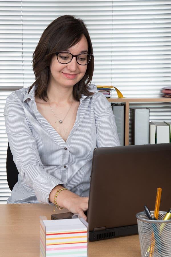 Glimlachende vrouw die haar laptop computer met behulp van op kantoor royalty-vrije stock foto's