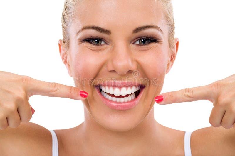 Glimlachende vrouw die in haar perfecte tanden richten stock fotografie