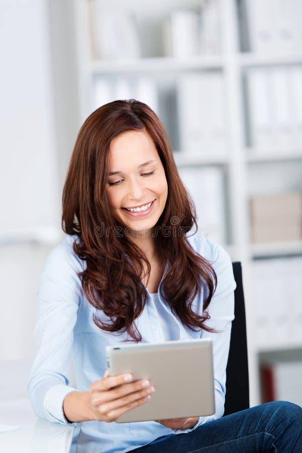 Glimlachende vrouw die haar tablet-PC lezen royalty-vrije stock foto's