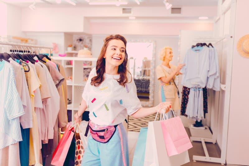 Glimlachende vrouw die heel wat dingen kopen terwijl het doen van het winkelen royalty-vrije stock foto