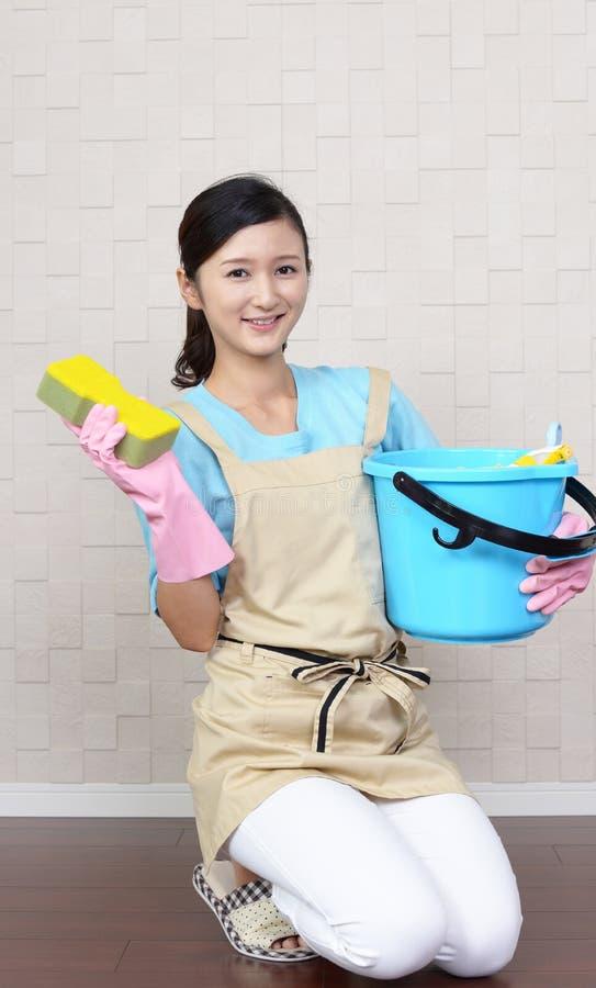 Glimlachende vrouw die het huis schoonmaken royalty-vrije stock afbeelding
