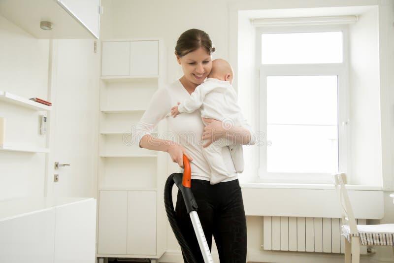 Glimlachende vrouw die het tapijt schoonmaken die een baby houden stock foto's