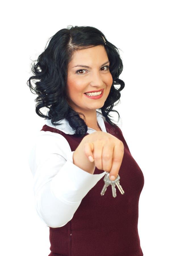 Glimlachende vrouw die huissleutels geeft stock foto's