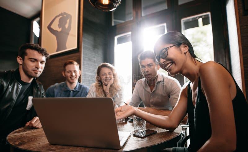 Glimlachende vrouw die iets op laptop tonen aan haar vrienden royalty-vrije stock foto's
