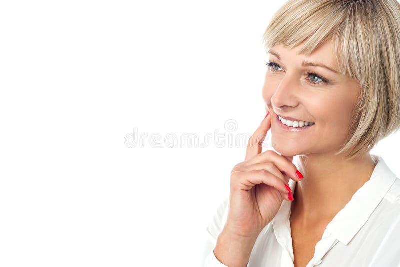 Glimlachende vrouw die iets veronderstellen royalty-vrije stock foto's
