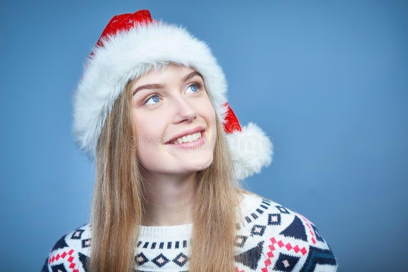 Glimlachende vrouw die Kerstmanhoed dragen die weg exemplaarruimte bekijken stock foto's