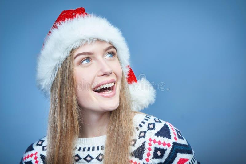 Glimlachende vrouw die Kerstmanhoed dragen die weg exemplaarruimte bekijken royalty-vrije stock afbeelding