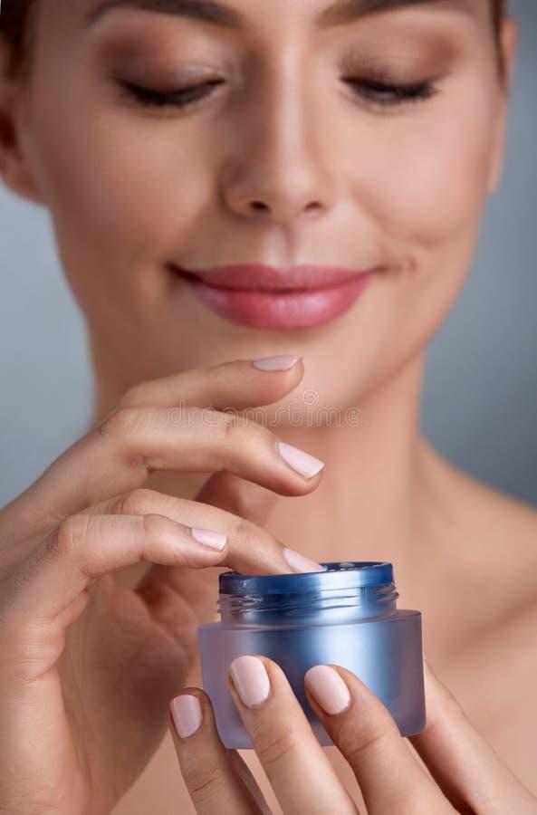 Glimlachende vrouw die kosmetische room gebruiken stock fotografie