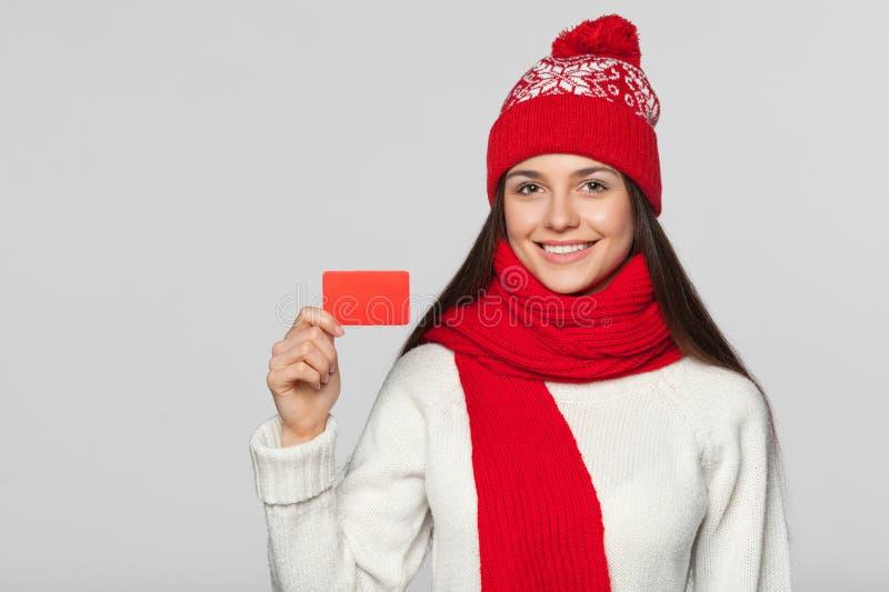Glimlachende vrouw die lege creditcard, de winterconcept tonen Gelukkig meisje in rode die hoed en sjaalholdingskaart, over grijs royalty-vrije stock foto