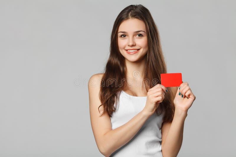 Glimlachende vrouw die lege creditcard in witte die t-shirt tonen, over grijze achtergrond wordt geïsoleerd royalty-vrije stock fotografie