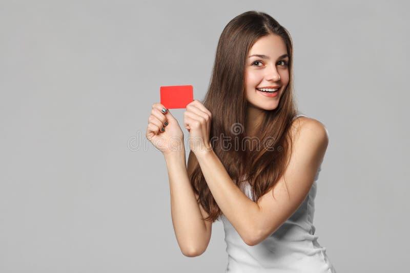 Glimlachende vrouw die lege creditcard in witte die t-shirt tonen, over grijze achtergrond wordt geïsoleerd royalty-vrije stock afbeelding