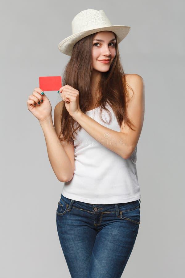 Glimlachende vrouw die lege creditcard in witte die t-shirt tonen, over grijze achtergrond wordt geïsoleerd stock afbeelding