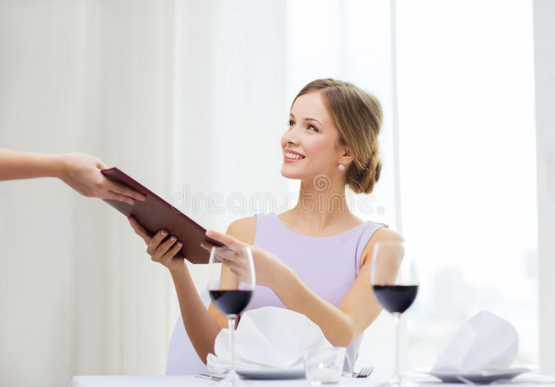 Glimlachende vrouw die menu geven aan kelner bij restaurant stock afbeelding
