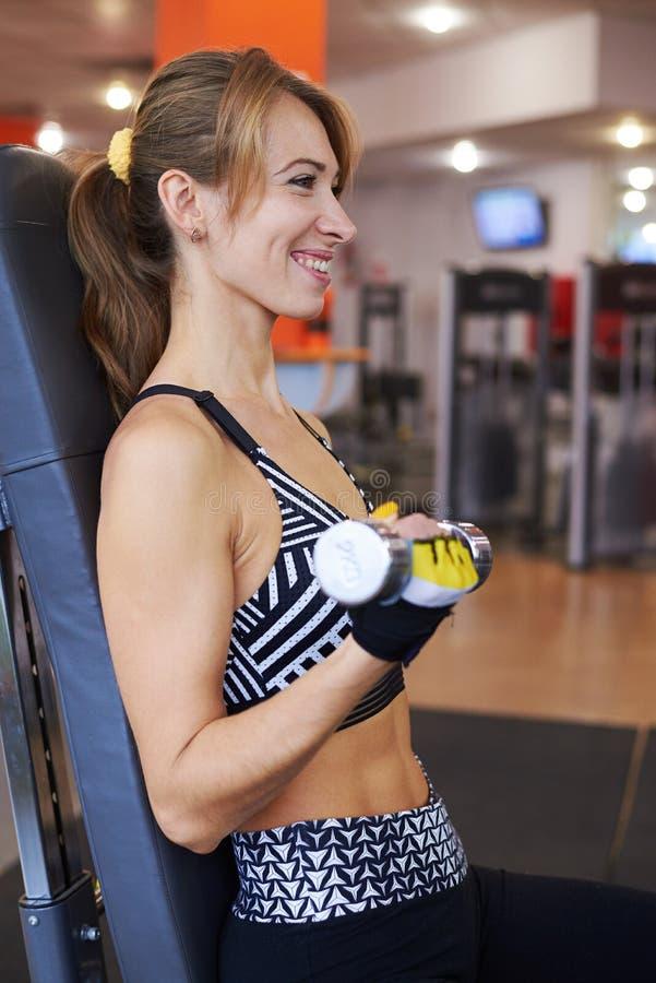 Glimlachende vrouw die met domoren bij gymnastiek uitoefenen royalty-vrije stock foto's