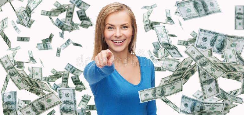 Glimlachende vrouw die met geld vinger op u richten stock afbeelding
