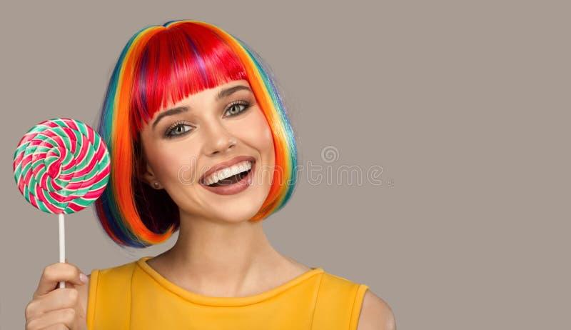 glimlachende vrouw die met helder kleurrijk haar grote lolly houdt royalty-vrije stock afbeeldingen