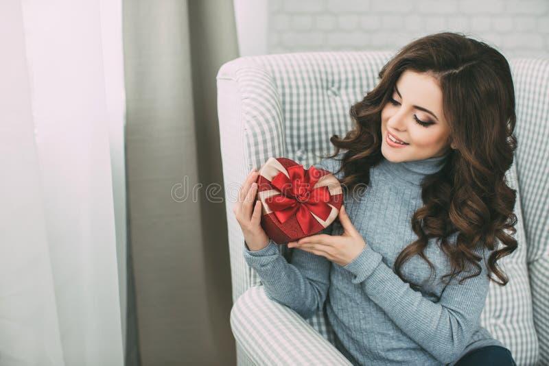 Glimlachende vrouw die met lang krullend haar een hart van de giftdoos houden stock afbeeldingen