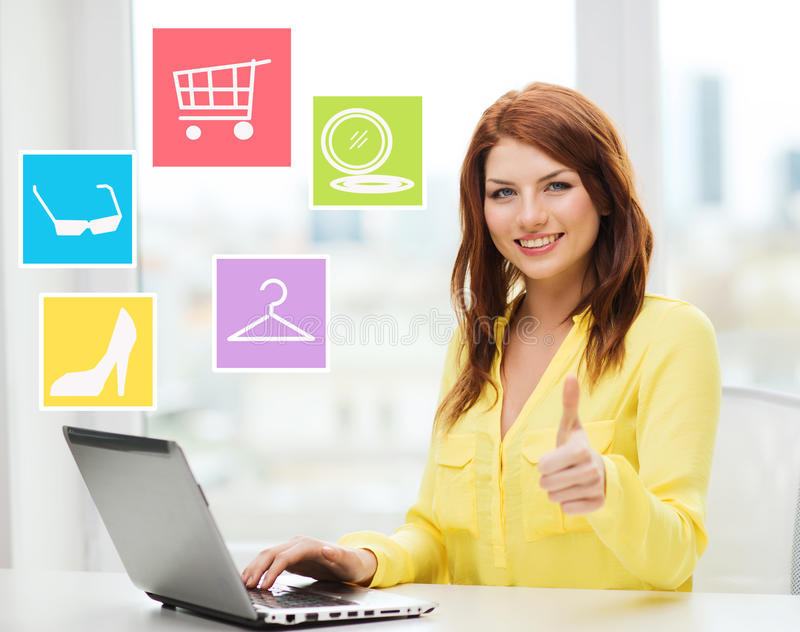 Glimlachende vrouw die met laptop online thuis winkelen stock afbeeldingen