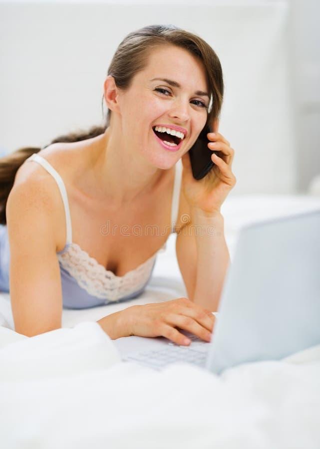 Glimlachende vrouw die met laptop telefoongesprek maakt royalty-vrije stock afbeeldingen