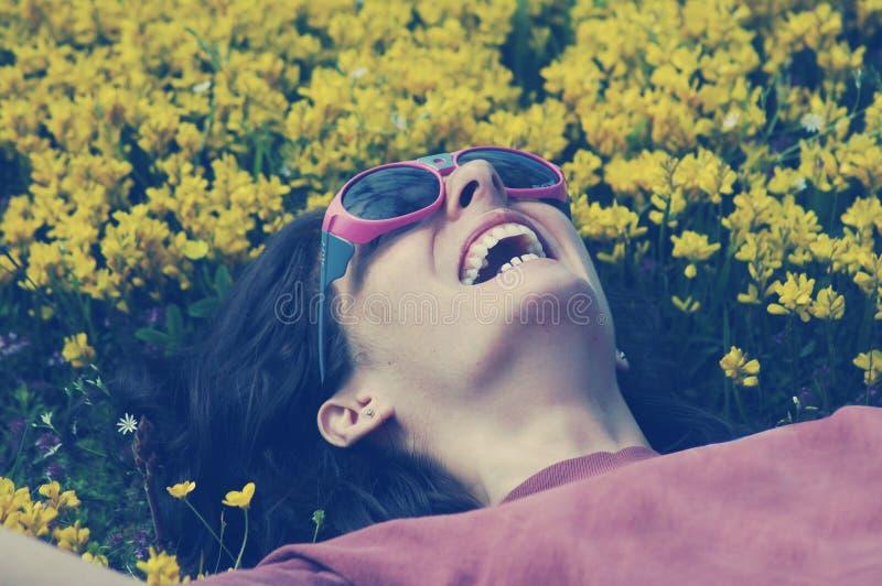 Glimlachende vrouw die met zonnebril op een weidehoogtepunt leggen met yello royalty-vrije stock afbeelding