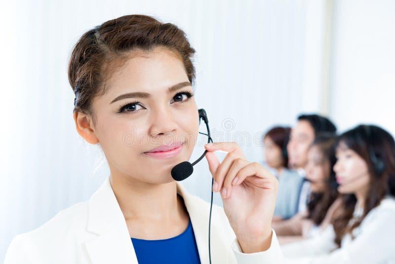 Glimlachende vrouw die microfoonhoofdtelefoon dragen als exploitant stock foto