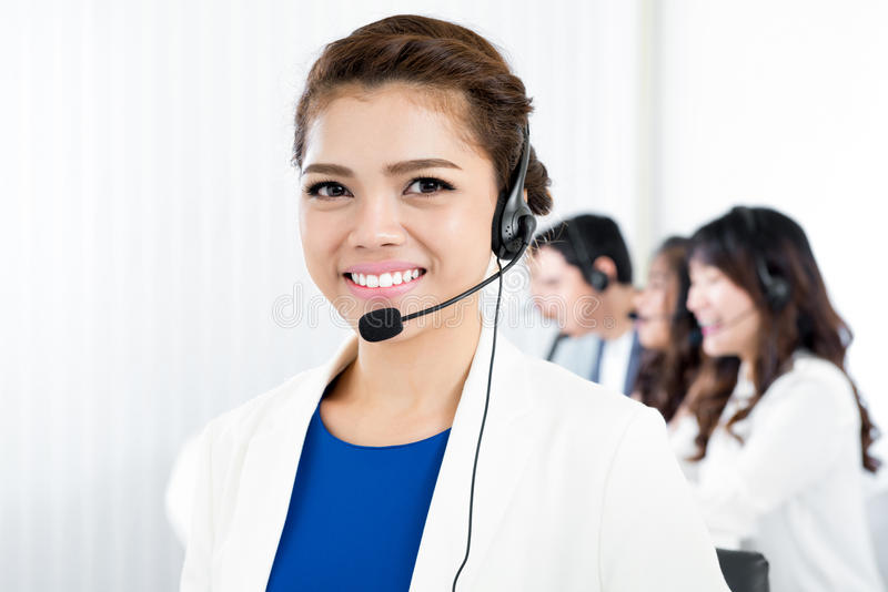 Glimlachende vrouw die microfoonhoofdtelefoon dragen als exploitant, telemarketer en call centrepersoneel stock foto's