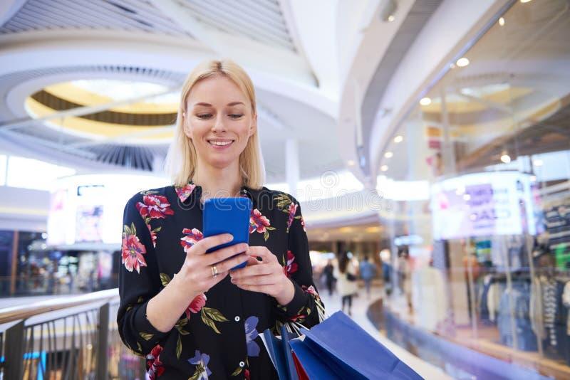 Glimlachende vrouw die mobiele telefoon in winkelcomplex met behulp van royalty-vrije stock afbeeldingen