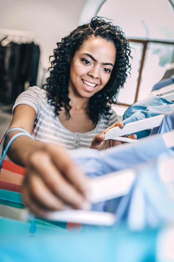 Glimlachende vrouw die nieuwe kleren kiezen royalty-vrije stock afbeelding