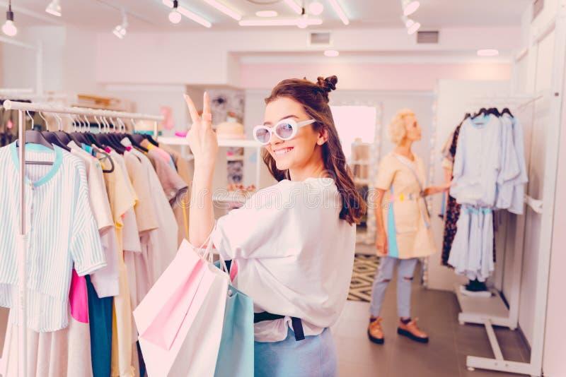 Glimlachende vrouw die nieuwe kleren kopen terwijl het doen van het winkelen royalty-vrije stock foto's